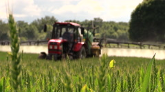 farmer spray agricultural tractor fertilizer on cereal field - stock footage