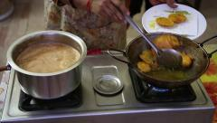 Vegetable pakoras are removed from oil & milky chai bubbles on stove in India. Stock Footage