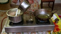 Indian woman heats oil for pakoras & adds milk to chai tea in India. Stock Footage