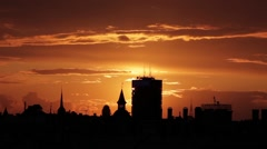 Dramatic clouds timelapse at sunset over a city skyline silhouette Stock Footage