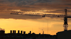 A timelapse of construction crane in action over a city skyline silhouette Stock Footage