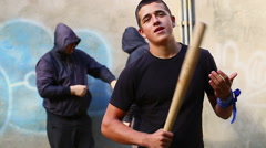 Aggressive teenager with a baseball bat with two mens behind - stock footage