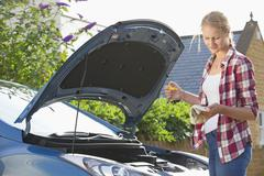 Woman checking oil level in car engine Stock Photos