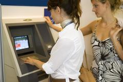 Women at an atm machine. Stock Photos
