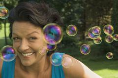 Stock Photo of a mature adult playing with bubbles.