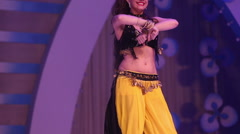 Girl dancing on stage in a yellow black national Indian suit Stock Footage