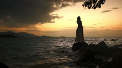 Woman standing on rock and looking to the horizon over sea Stock Footage