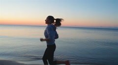 Young woman with a slender figure is engaged in gymnastics at sea at sunrise Stock Footage