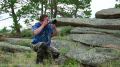 Photographer taking a picture in wild nature Stock Footage