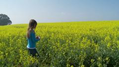 Young girl walking through canola flowers Stock Footage