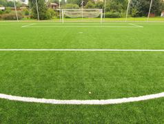 Closeup view to white lines on artificial grass field on football playground. Stock Photos