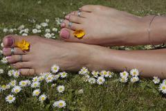female feet on grass lawn with flowers - stock photo