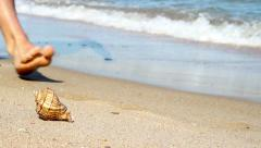 Sea shell on the beach and human legs Stock Footage