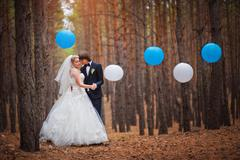 Happy bride and groom walking in the forest Stock Photos