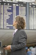 a businessman looking at the flight schedules. - stock photo