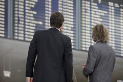 Businessmen looking at the flight schedules. Stock Photos