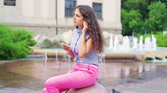 Woman relaxing and listening music on the phone next to the fountain Stock Footage