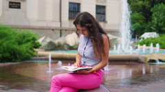 Woman sitting next to the fountain and reading interesting book Stock Footage