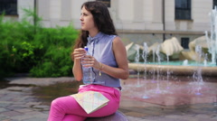 Woman drinking water from plastic bottle and sitting next to the fountain Stock Footage