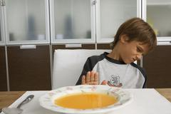 boy sitting with a bowl of soup. - stock photo