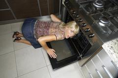 a woman kneeling down to look at an oven. - stock photo