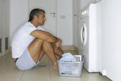 man sitting in front of a washing machine. - stock photo