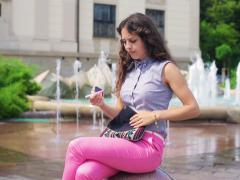 Woman relaxing next to the fountain and bringing out mirror and lipgloss Stock Footage