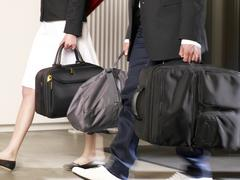 couple carrying their luggage in a hotel. - stock photo