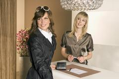 Stock Photo of close-up of a woman standing at a checkout counter with a receptionist