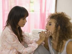 Close-up of a young woman applying lipstick on her friend Stock Photos
