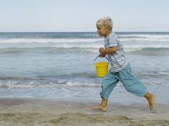Stock Photo of a boy running on the beach with a sand pail