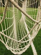 Hang bended soccer nets, football net. Plastic grass and white painted line - stock photo