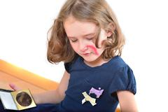 Little cute girl posing while painting her face - stock photo