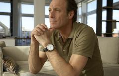 man sitting with his hands clasped - stock photo