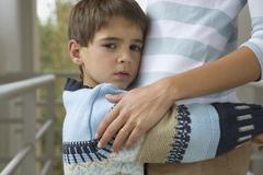 Young boy hugging his mother Stock Photos