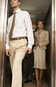 Businessman exiting from an elevator with a businesswoman standing behind him - stock photo