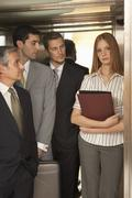 Three businessmen looking at a businesswoman standing in an elevator - stock photo