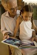 Grandfather reading to his granddaughter Stock Photos