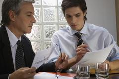 Two businessmen sitting at a desk and looking at documents in an office Stock Photos
