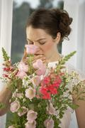 Mid adult woman sneezing behind a bouquet of flowers Stock Photos