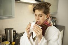 Close-up of a mid adult woman sneezing in the kitchen Stock Photos