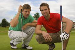 Two mid adult men crouching on a golf course and smiling - stock photo