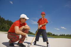 Side profile of a mid adult man giving golf training to his son Stock Photos