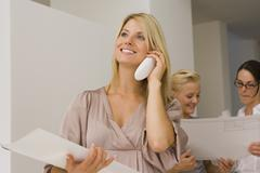Businesswoman talking on a cordless phone with two businesswomen discussing in Stock Photos