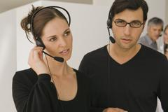 Two customer service representatives wearing headsets in an office Stock Photos