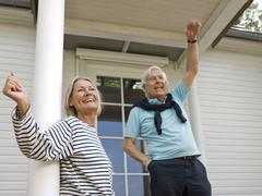 Senior couple waving on veranda Stock Photos