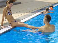 Man tugging woman's leg at pool Stock Photos