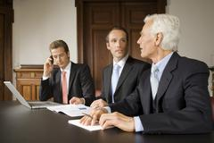 Businessmen in board meeting - stock photo