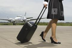 Low section view of a woman pulling her luggage Stock Photos