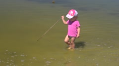 A child girl plays in a pond water during family weekend - carefree childhood Stock Footage